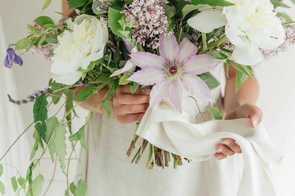 lavender-and-white-bouquet-with-long-silk-ribbon-streamer-on-the-stems-being-gently-held-in-frame
