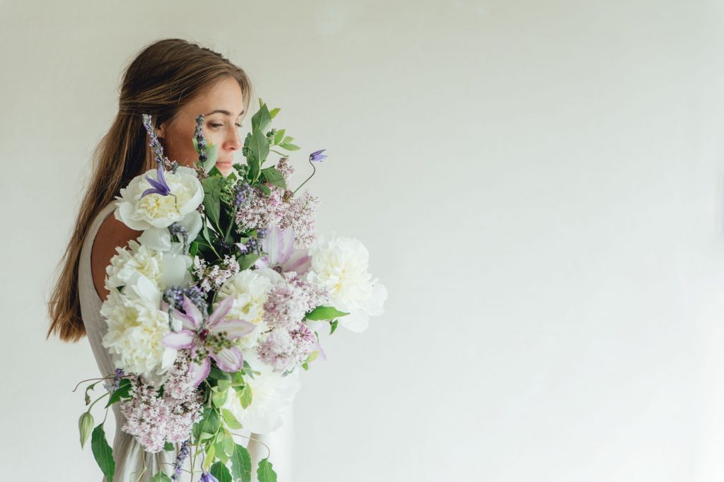 side-profile-of-girl-holding-lavender-bouquet-with-peony-lavender-and-clematis