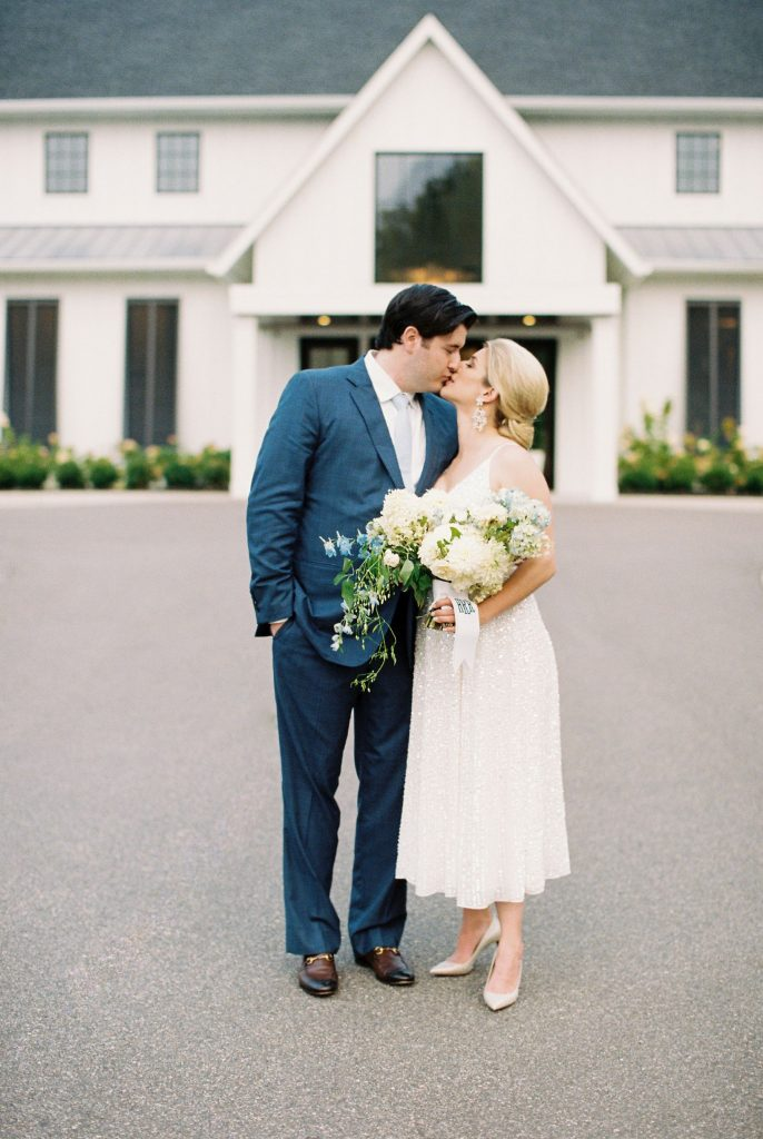 bride-and-groom-standing-in-front-of-venue-kissing
