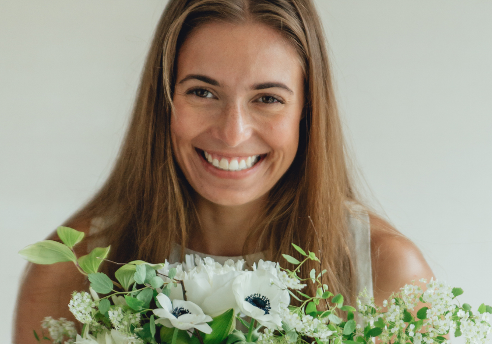 smiling-girl-holding-flowers-title-how-to-choose-your-wedding-florist