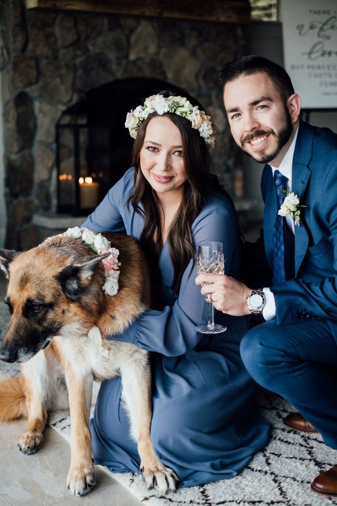 bride and groom in blue, leaning down to pet a german shepard. The bride and dog are wearing coordinating flower crown and collar
