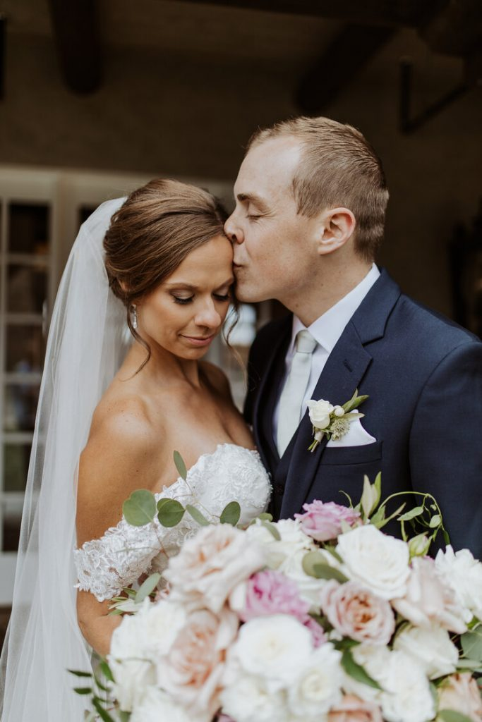 groom-kissing-brides-forehead-with-bouquet-in-foreground