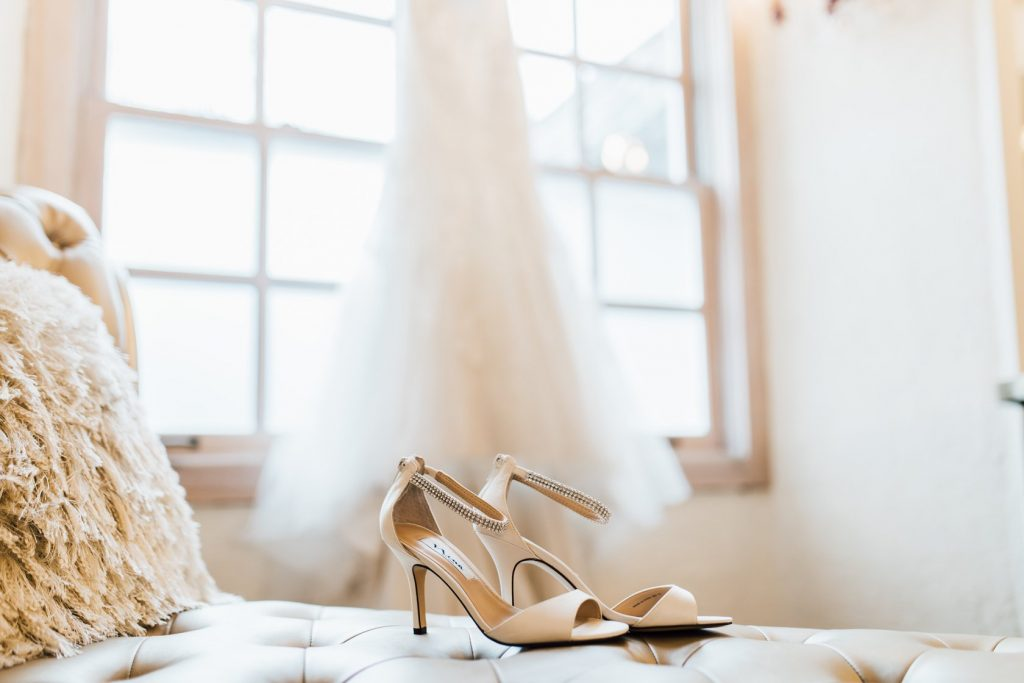 bridal-shoes-in-focus-with-gown-handing-in-window-behind