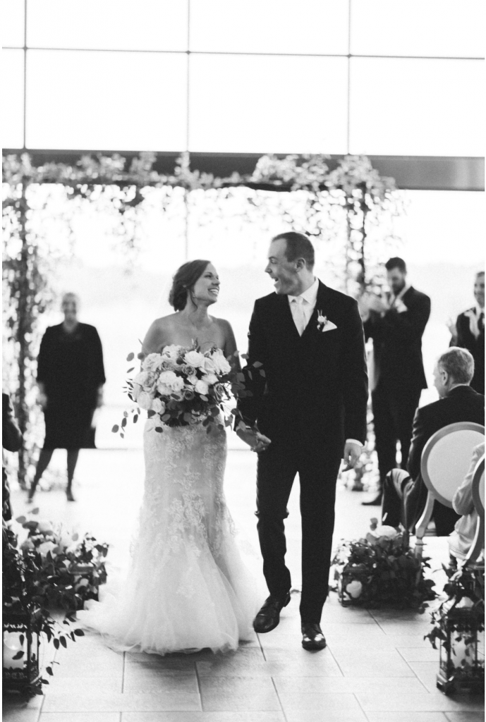 bride-and-groom-recessing-smiling-at-each-other-black-and-white
