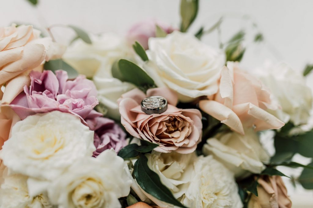 engagement-ring-and-wedding-band-on-brides-flowers