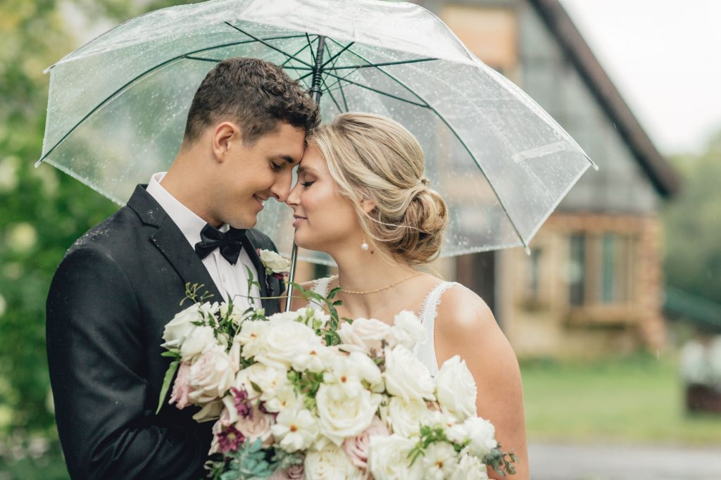 bride and groom touching foreheads underneath a clear umbrella
