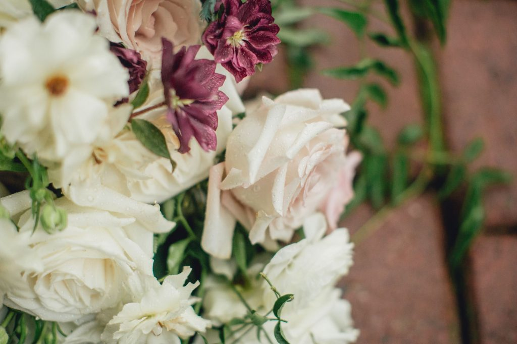 close up of blush rose and plum hellebore in a bouquet