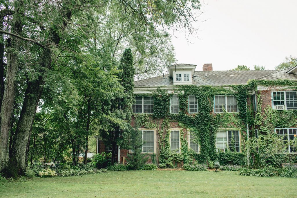 photo of ivy covered brick building with lush green grass and trees