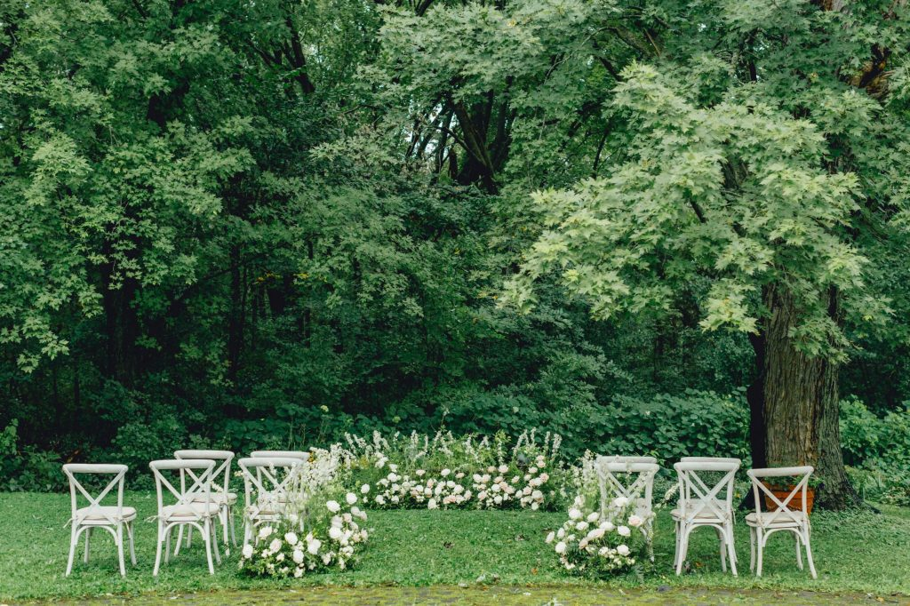 wedding ceremony in fully wooded clearing with white cross back chairs and white flowers